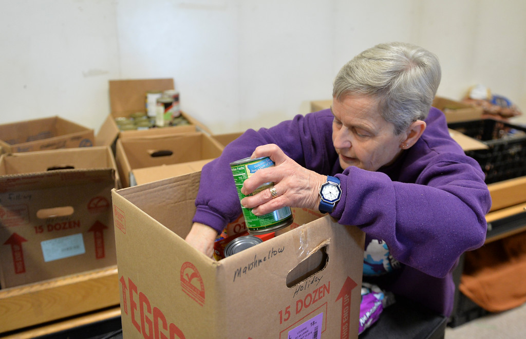 Justin Sheely | The Sheridan Press<br /> Volunteer Paula Wittmer loads up boxes with items needed for a Thanksgiving Day meal Monday at the People Assistance Food Bank on N. Main Street. The Food Bank's founder Dan Lick died September 30, 2016 – the volunteers are working to honor Lick's vision this holiday season.