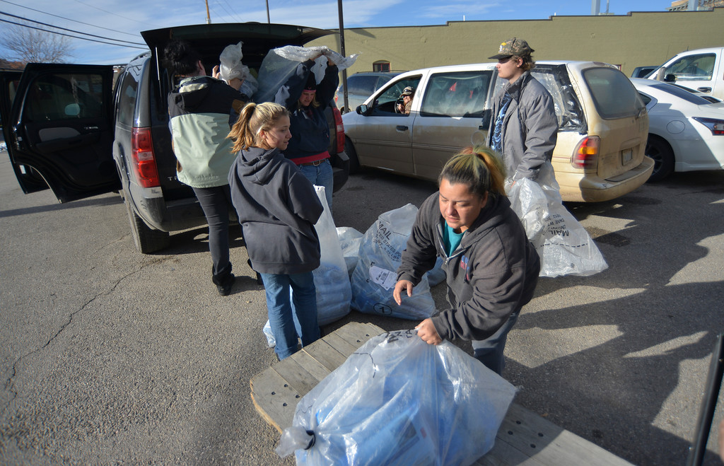 Justin Sheely | The Sheridan Press<br /> Contract paper carrier Sara Williams, center, and daughter Bambi Williams, left, load bags filled with print editions into their their vehicle as staff prepare for the county-wide free distribution of the Thanksgiving Day paper Wednesday at The Sheridan Press. More than 12,000 papers were distributed to homes across Sheridan County for the free edition of The Sheridan Press.