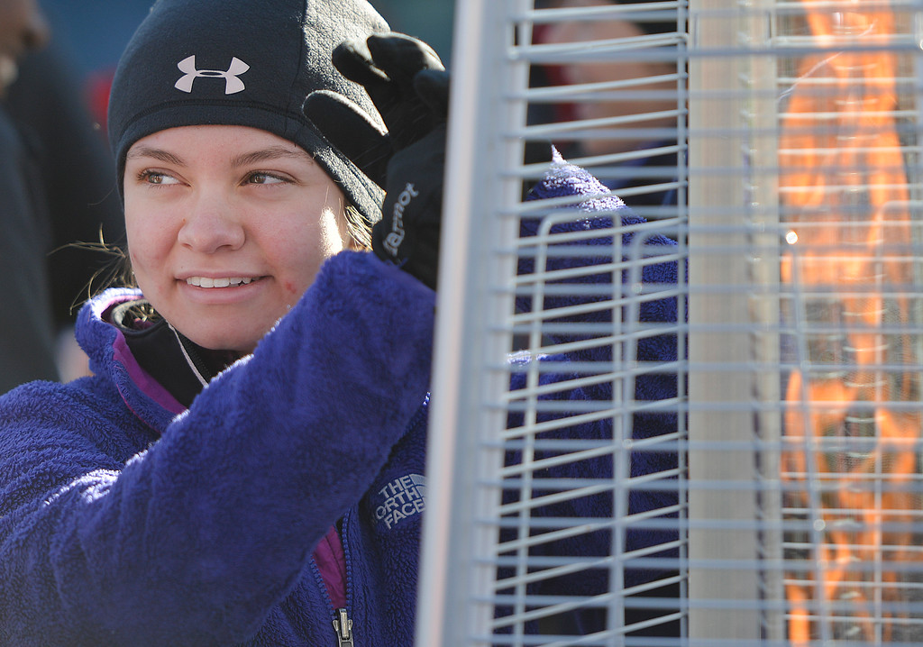 Justin Sheely | The Sheridan Press<br /> Tailor Geeting warms her hands by a gas fire as participants wait prior to the 38th annual Turkey Trot Thursday morning at Kendrick Park. Proceeds from the event support the Sheridan Junior High School and Sheridan High School Cross Country and Track and Field programs.