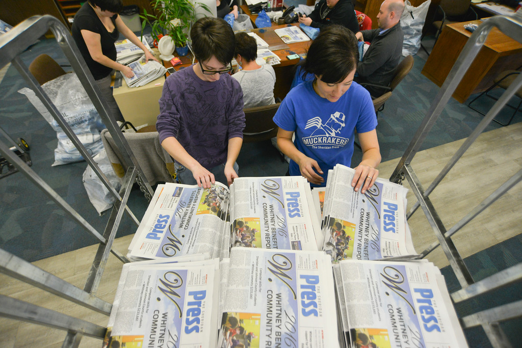 Justin Sheely | The Sheridan Press<br /> Ryan Woody, left, and Janea LaMeres pulls copies from cart to roll and bag for the county-wide free distribution of the Thanksgiving Day paper Wednesday at The Sheridan Press. More than 12,000 papers were distributed to homes across Sheridan County for the free edition of The Sheridan Press.