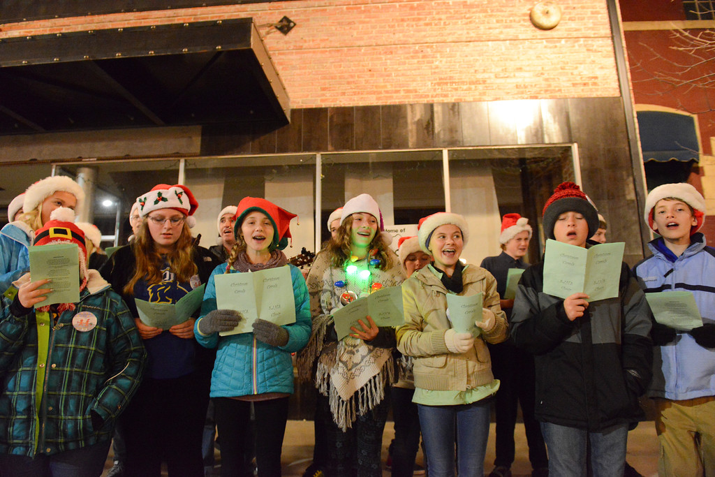Justin Sheely | The Sheridan Press<br /> Sheridan Junior High School choir members sing carols during the annual Christmas Stroll Friday on Main Street. The event is to encourage the community to shop local and and provides fun activities for children, including wagon rides and pictures with Santa.