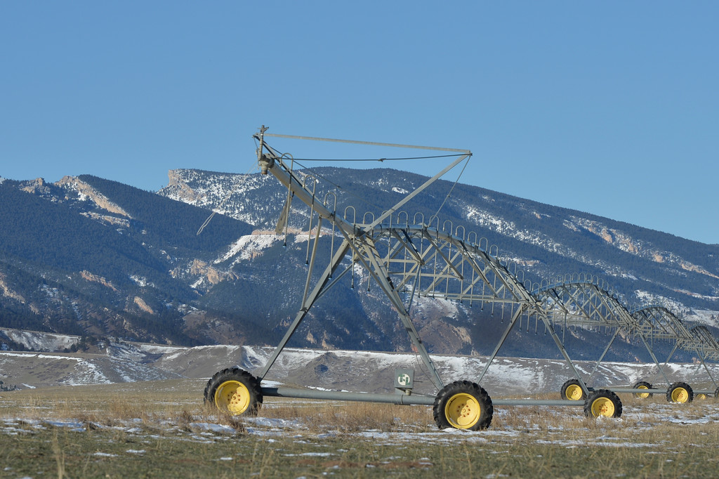 Justin Sheely | The Sheridan Press<br /> Irrigation equipment stands in front of the Bighorn Mountains by Beckton Road Wednesday morning. Highway 14 is visible along with locally prominent Steamboat Point, left. Weather is expected to be cooler with chances of light snow throughout the week.