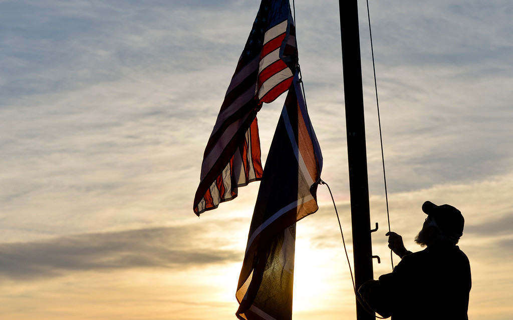 Justin Sheely | The Sheridan Press<br /> A state park employee raises the flags Saturday morning at Fort Phil Kearny State Historic Site.