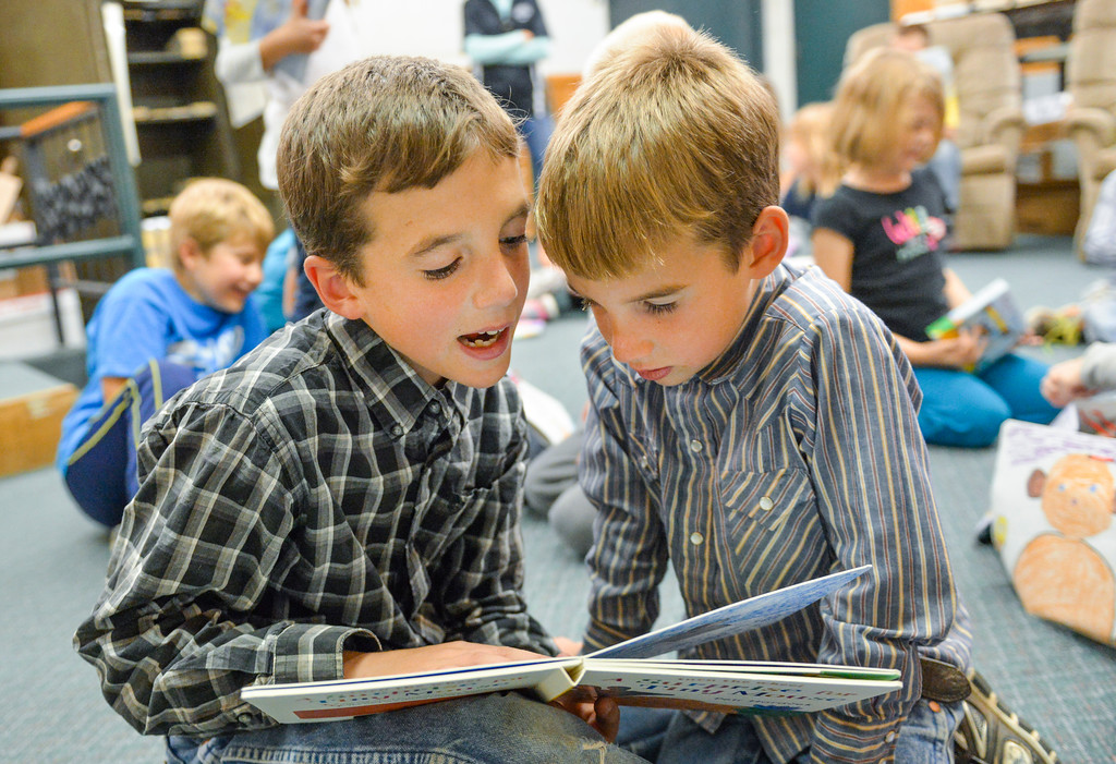 Justin Sheely | The Sheridan Press<br /> Slack School fifth-grader Aaron Hartfeld, left, reads aloud to Isaac Hartfeld after picking out children's books Thursday at Sheridan Stationery Books and Gallery on Main Street. The students raised money to purchase 36 books for newborns at Sheridan Memorial Hospital. They also made personal envelopes to put the books in before delivering to the maternity ward. The books are intended to be given to families of newborns delivered at SMH.