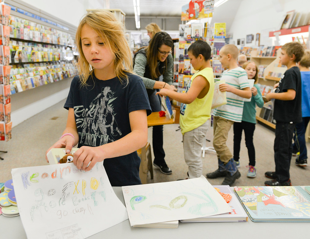 Justin Sheely | The Sheridan Press<br /> Tongue River Elementary School second-grader Masa Hanft puts a children's book for babies in to her envelope Thursday at Sheridan Stationery Books and Gallery on Main Street. The students raised money to purchase 36 books for newborns at Sheridan Memorial Hospital. They also made personal envelopes to put the books in before delivering to the maternity ward. The books are intended to be given to families of newborns delivered at SMH.