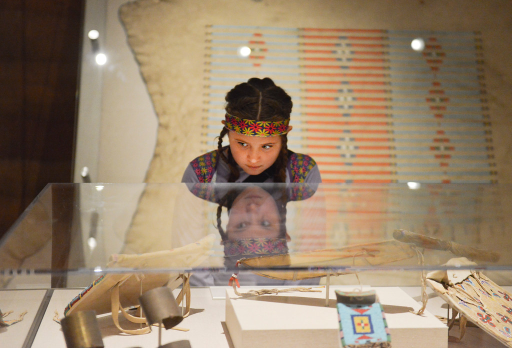 Justin Sheely | The Sheridan Press<br /> Nine-year-old Aurianna Ottema looks at items in a display in the Plains Nations Exhibit during Things that Go Bump in the Night event Saturday at the Brinton Museum. Guests were given a list of items to find in the gallery to learn about the Native American history and were rewarded with a bag of treats after completing their tasks.