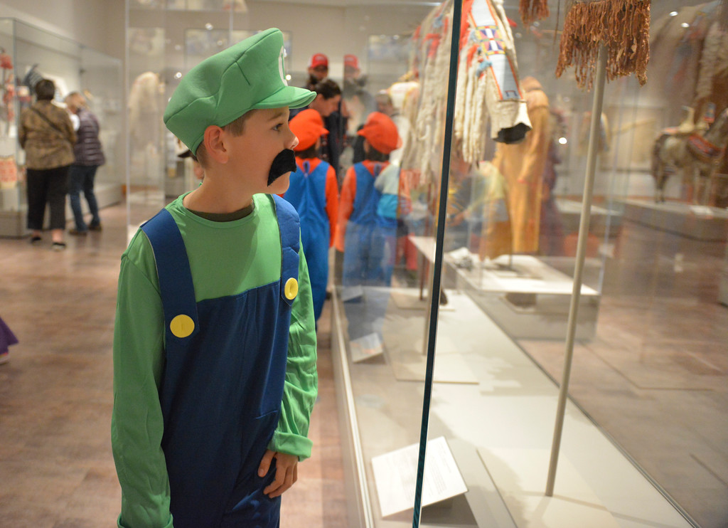 Justin Sheely | The Sheridan Press<br /> Eight-year-old Alex Eisenman looks for artifacts in the Plains Nations Exhibit during Things that Go Bump in the Night event Saturday at the Brinton Museum. Guests were given a list of items to find in the gallery to learn about the Native American history and were rewarded with a bag of treats after completing their tasks.
