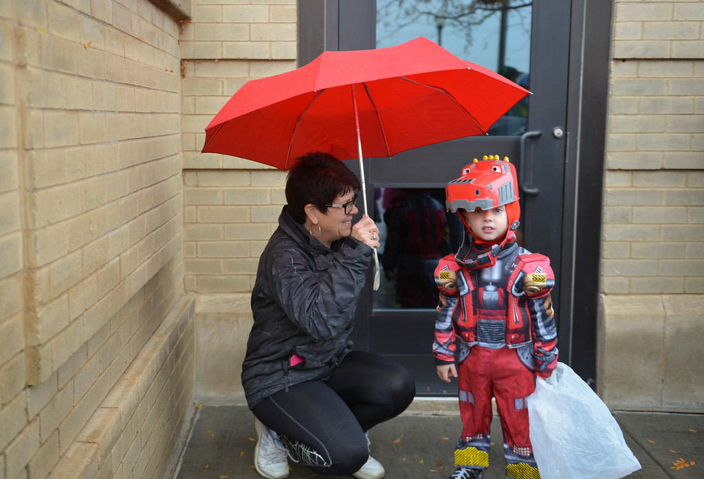 Justin Sheely | The Sheridan Press<br /> Peggy Miller huddles next to her grandson Max Schutte, 3, during the Sheridan Jaycees Halloween Parade Saturday outside of City Hall in downtown Sheridan. Dozens of participants came to the parade despite the rain.