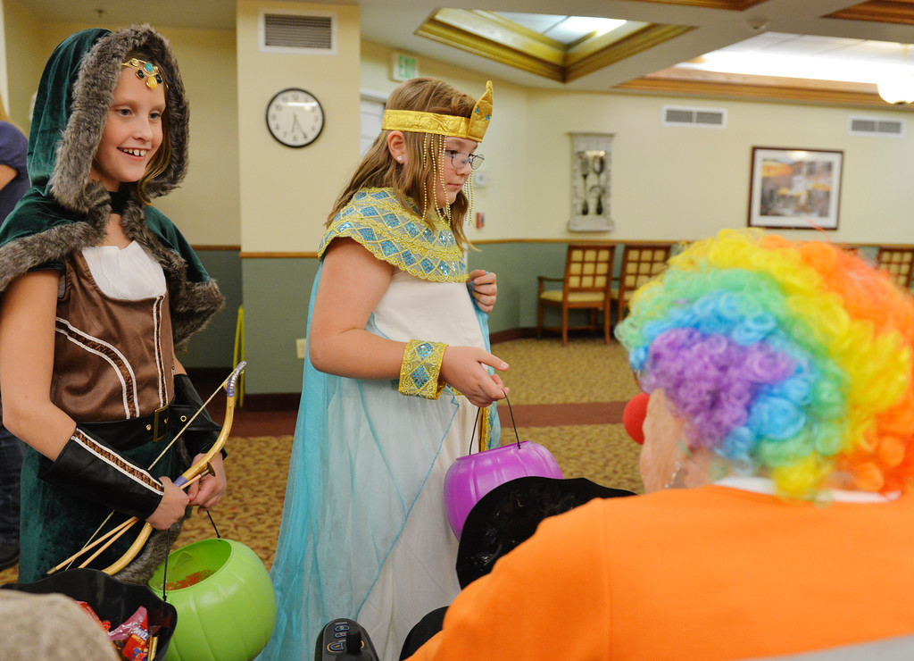Justin Sheely | The Sheridan Press<br /> Nine-year-old Alexia Oss, as an archer, left, and Delenn Luyher, as Cleopatra visit the residents during Halloween at Sugarland Ridge Thursday evening. Brookdale residents gathered to hand out candy, provide games and activities for the children of the community to enjoy for free.