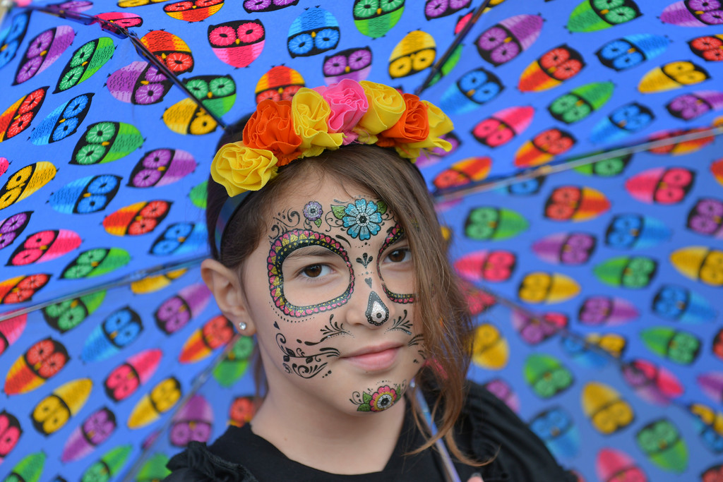 Justin Sheely | The Sheridan Press<br /> Nine-year-old Sydney Dixon stands under her umbrella adorned with Day of the Dead themed tattoos during the Sheridan Jaycees Halloween Parade Saturday outside of City Hall in downtown Sheridan. Dozens of participants came to the parade despite the rain.