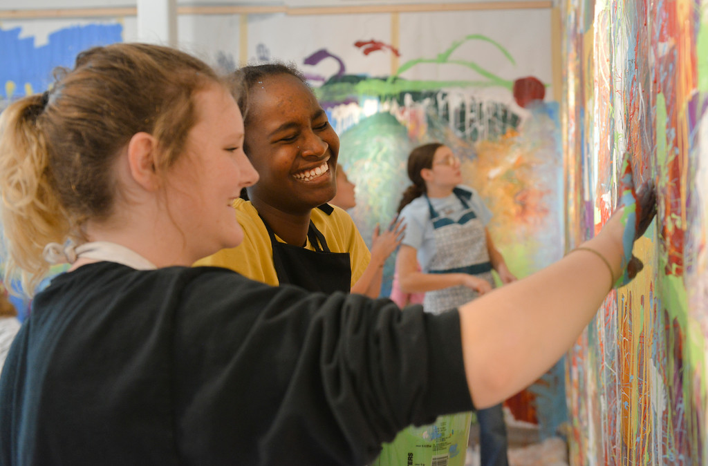 Justin Sheely | The Sheridan Press<br /> Sheridan Junior High School students Samantha Burgess, left, and Hallie Sweeney laugh as they paint during an abstract workshop Thursday in the Whitney Center for the Arts building at Sheridan College. Art instructor Jason Lanka lead a presentation on abstract art and assigned the students to pick complex emotions and create an abstract painting that would convey that emotion. The junior high students were also shown examples in Neltje's work, which is on display throughout the halls of the art center. The workshop is part of an outreach effort by art instructors at the college. The junior high students' work is on display in the Neltje Student Gallery at the Whitney Center for the Arts and open to the public through November 15.