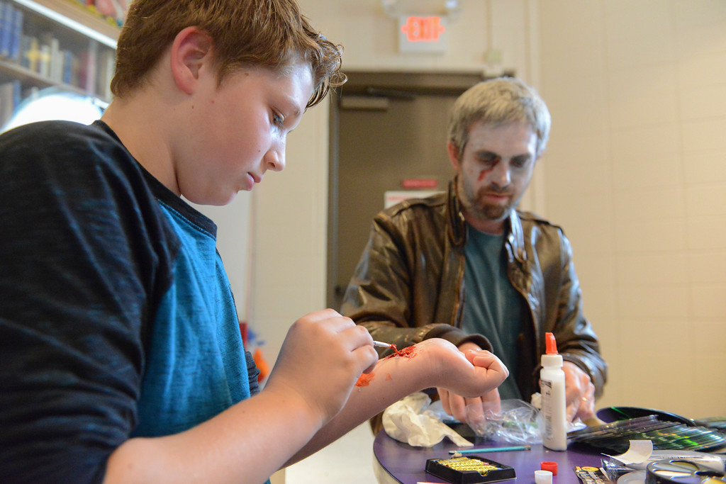 Justin Sheely | The Sheridan Press<br /> Eleven-year-old Ethan McGill makes bite marks on his arm during the Tween Zombie Fest Tuesday at the Sheridan County Fulmer Public Library. The event focused on low-tech ways to create zombie makeup for kids. The Zombie Fest is part of the children's library Tween Program – intended to provide engaging activities for pre-high school youth.