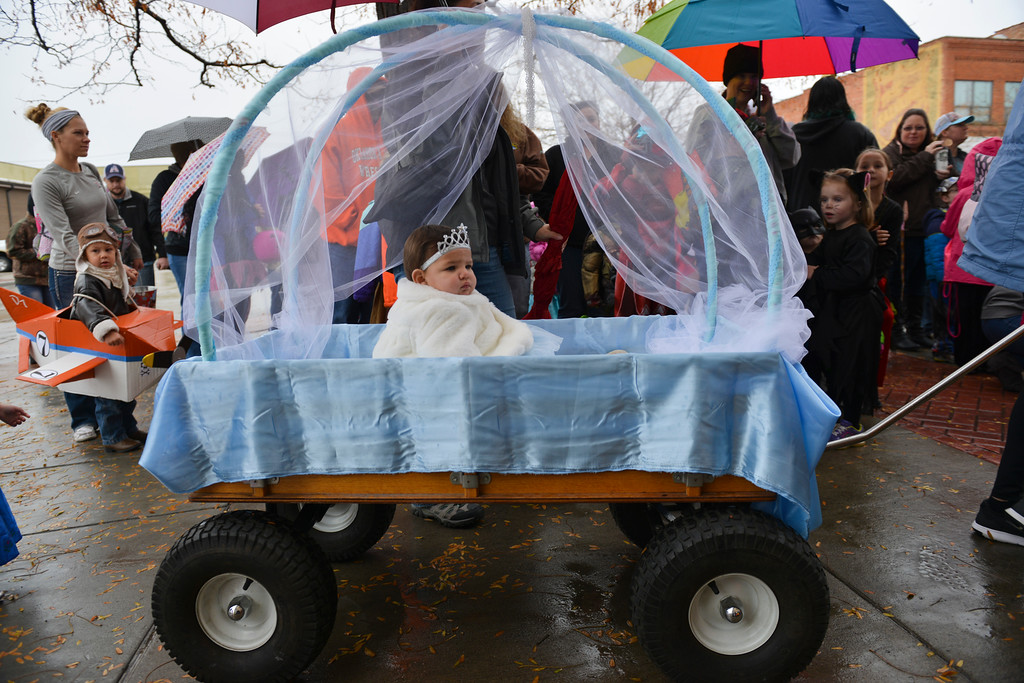 Justin Sheely | The Sheridan Press<br /> Eight-month-old Audrey Curiel is pulled in a Cinderella-themed carriage during the Sheridan Jaycees Halloween Parade Saturday outside of City Hall in downtown Sheridan. Dozens of participants came to the parade despite the rain.