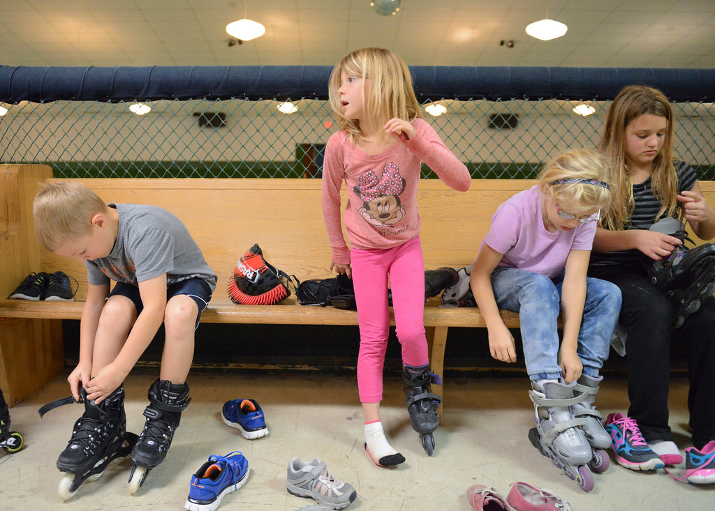 Justin Sheely | The Sheridan Press<br /> First-grader Molly Pavey, middle, stands up as she tries on a pair of roller blades during the YMCA's Big Horn Fun Day Friday at Scotty's Skate Castle. The YMCA's Fun Friday program provides fun activities for elementary students in the Big Horn district since Sheridan County School District 1 does not have class on Fridays.