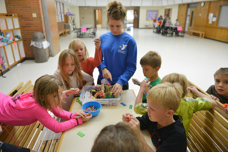 Justin Sheely | The Sheridan Press<br /> Kids swarm around a table with beads and string for a Jamaican bracelet craft activity during the after school program at the YMCA Tuesday.