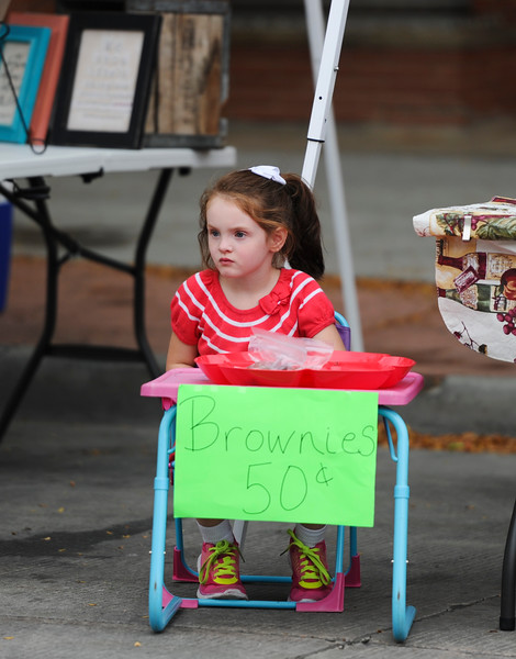 Justin Sheely | The Sheridan Press<br /> Five-year-old Sophi Cox waits as she sells her homemade brownies during the last Farmers Market of the season Thursday on Grinnell Plaza.