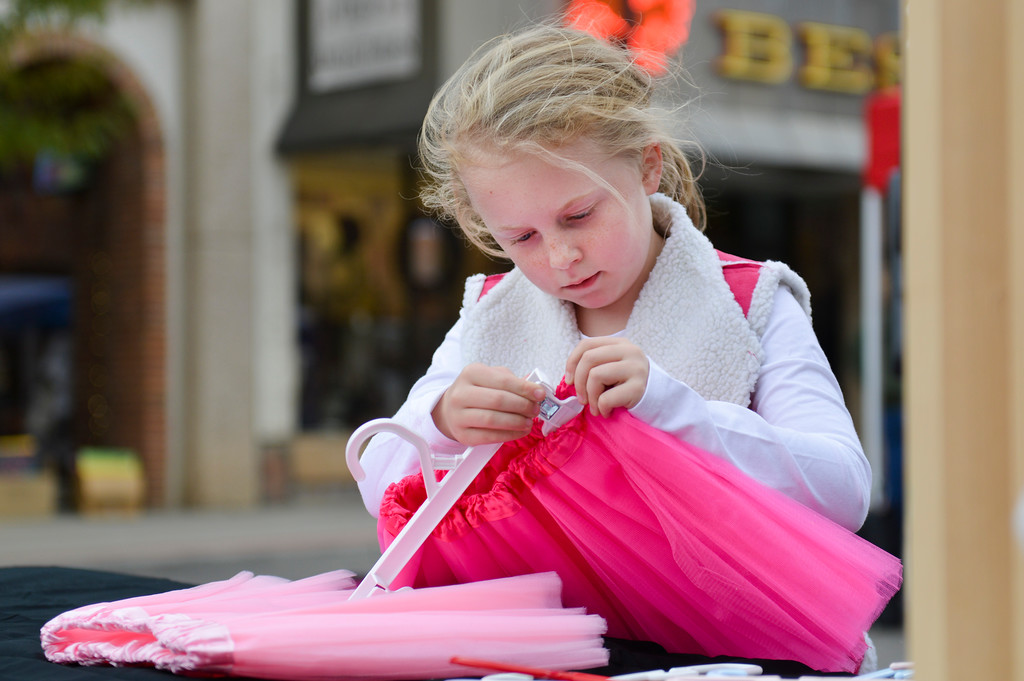 "Justin Sheely | The Sheridan Press<br /> Seven-year-old Luci Raymond of Ranchester clips a skirt to a hanger for her girls' boutique ""Lulu's Closet"" during the final Third Thursday Street Festival on Main Street. Raymond buys and sells wholesale cloths that she picks out with the help of her family for her boutique aimed at young girls."