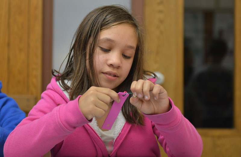 Justin Sheely | The Sheridan Press<br /> Third-grader Juliann Amende ties a string for a Jamaican bracelet craft activity during the after school program at the YMCA Tuesday.