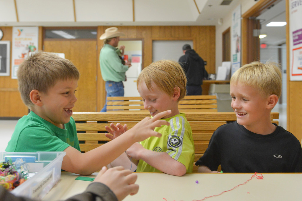 Justin Sheely | The Sheridan Press<br /> First graders, from left, Adam Bauers, Kal Condos and Cooper Berry distract each while in a Jamaican bracelet craft activity during the after school program at the YMCA Tuesday.