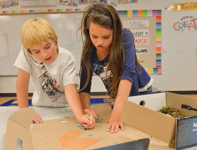 Justin Sheely | The Sheridan Press<br /> Third-graders Caiden Maurer, left, and Melanie Wiggins-Fulciniti draw a sunset on the back of their diorama during an after school program Wednesday at Coffeen Elementary School. The activity was lead by Joey's Flyfishing as part of a 6-week course, twice a week. The nonprofit organization had previously took the students to a local pond to learn about fish habitat and the students gathered materials to use for their diorama projects to illustrate the ecology.