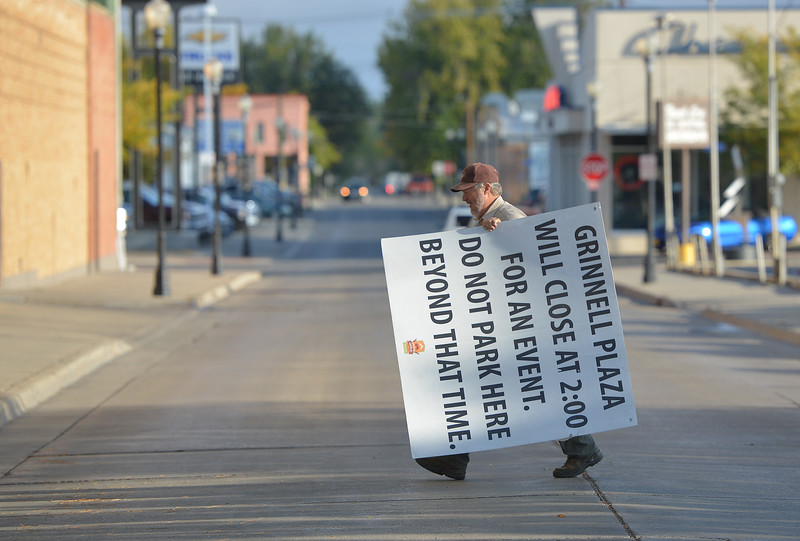 Justin Sheely | The Sheridan Press<br /> Volunteer Clark McClung carries a sign across Gould Street at Grinnell Thursday morning in preparation for the Farmers Market later that day. McClung says that volunteers try to put up parking signs as early as 8 a.m. to make sure Grinnell Plaza is clear of vehicles in time for setup in the afternoon. Next Thursday will be the last Farmers Market of the season.