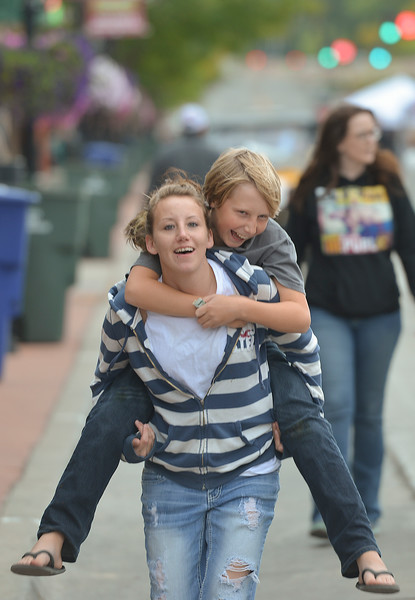 Justin Sheely | The Sheridan Press<br /> Twelve-year-old Derrick Bates gets a piggy-back ride from Desiree Fresorger during the final Third Thursday Street Festival on Main Street.