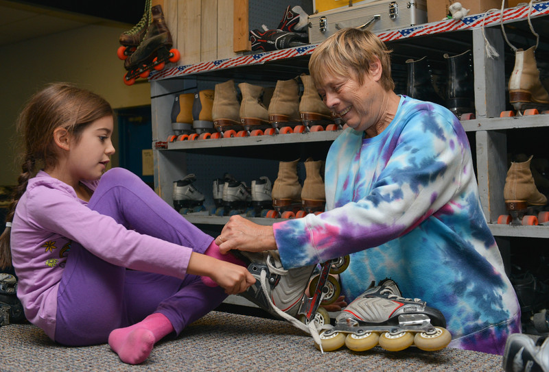 Justin Sheely | The Sheridan Press<br /> First-grader Lillian Sutphin sits on the counter as owner Gail Sidletsky helps her with sizing roller blades during the YMCA's Big Horn Fun Day Friday at Scotty's Skate Castle. The YMCA's Fun Friday program provides fun activities for elementary students in the Big Horn district since Sheridan County School District 1 does not have class on Fridays.