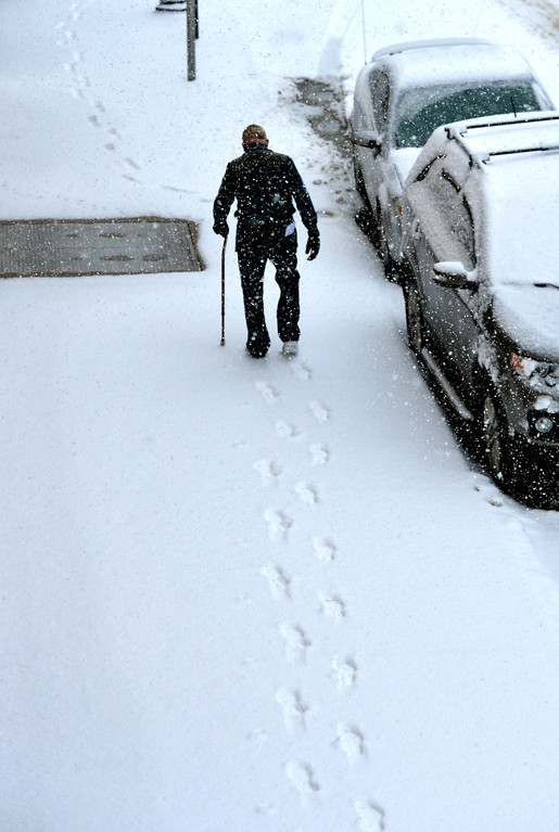Justin Sheely | The Sheridan Press<br /> A man walks over the snowy sidewalk in downtown Sheridan Tuesday morning. Sheridan County can expect snow accumulation from 3 to 6 inches according to a winter weather advisory issued by The National Weather Service of Billings, Montana.