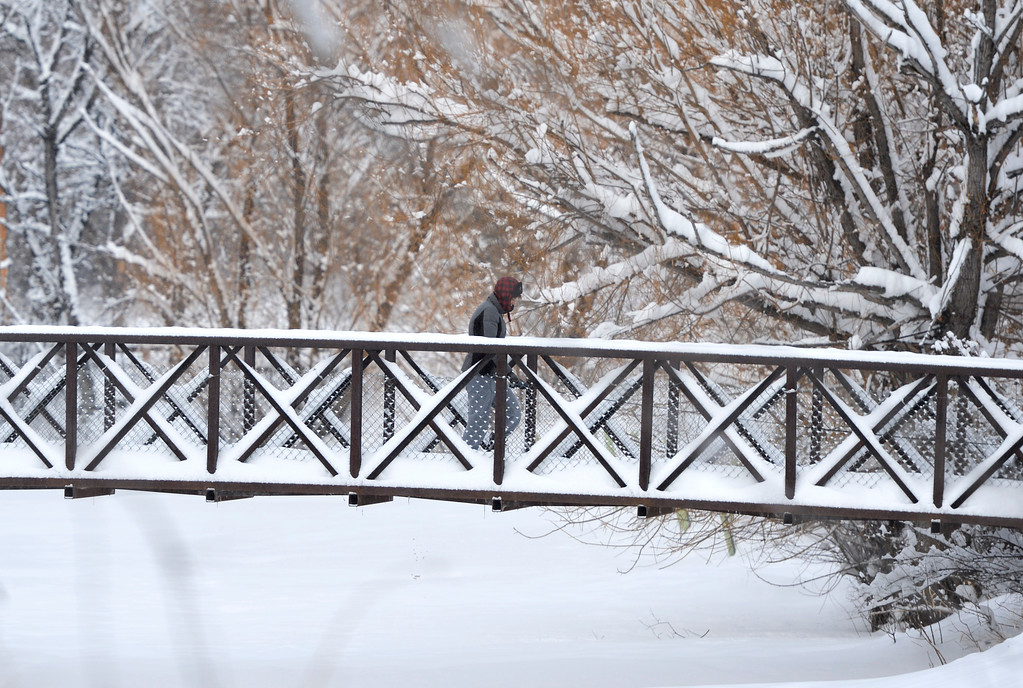 Justin Sheely | The Sheridan Press<br /> A walker crosses the bridge over Big Goose Creek at Kendrick Park Wednesday morning. Up to ten inches of snow accumulation was reported in parts of Sheridan County.