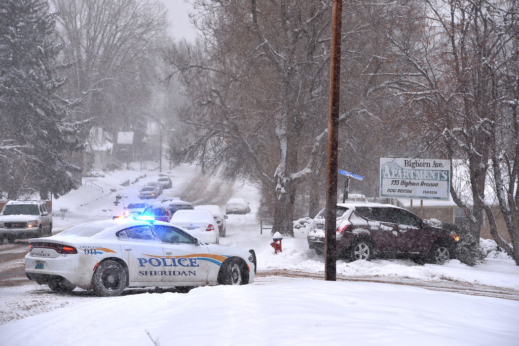 Justin Sheely | The Sheridan Press<br /> Law enforcement direct traffic away from the scene where a vehicle slid off the road into private property Tuesday afternoon on Big Horn Avenue. Snow accumulation led to dangerous driving conditions in the city of Sheridan.