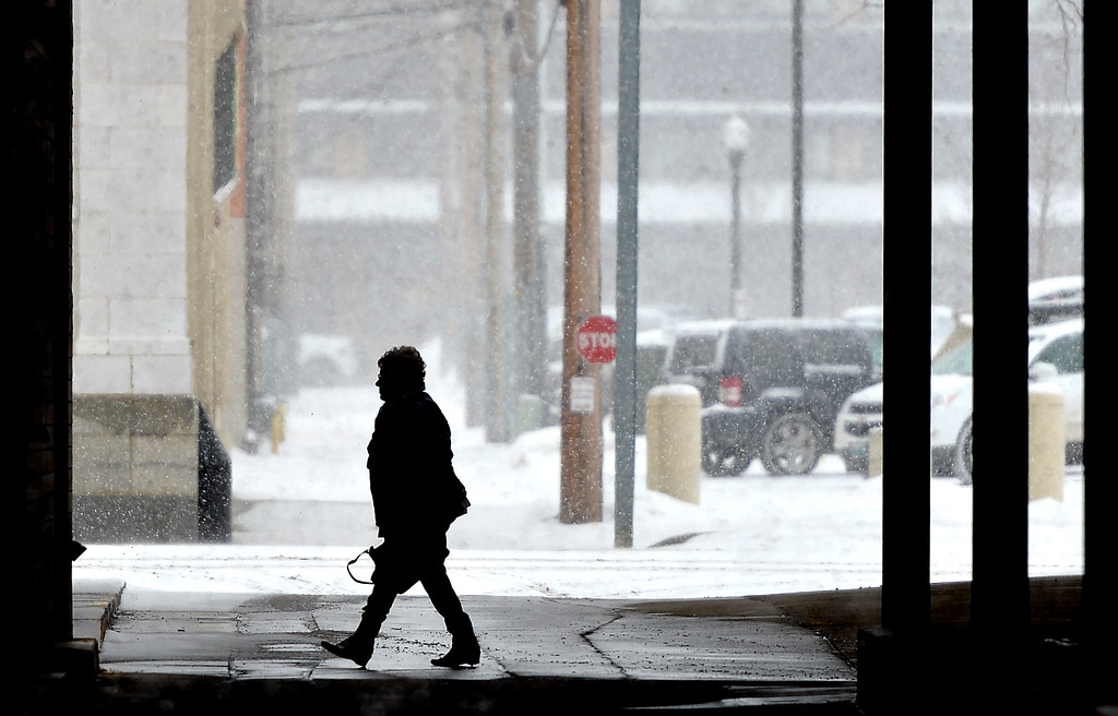 Justin Sheely | The Sheridan Press<br /> A woman walks under the public parking garage as snow falls Tuesday morning in Sheridan. Sheridan County can expect snow accumulation from 3 to 6 inches according to a winter weather advisory issued by The National Weather Service of Billings, Montana.