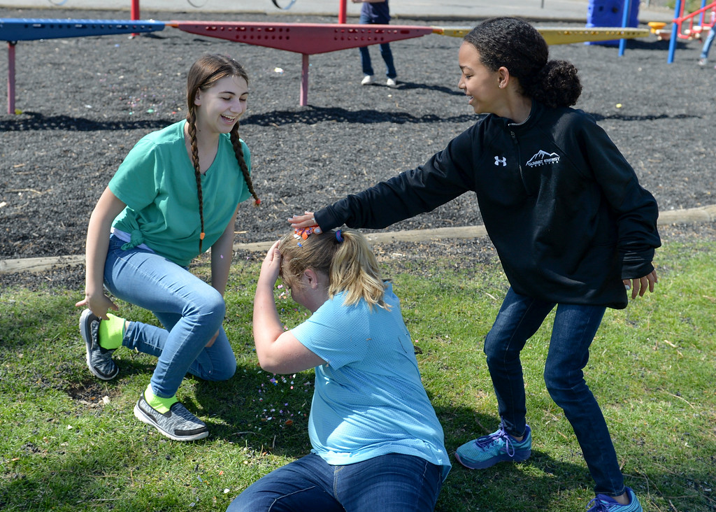 Justin Sheely   The Sheridan Press<br /> Gigi Miller, reacts as Layne Sweeney cracks an egg over Julia Smart's head during a hunt for Mexican Cascarones Easter Eggs Thursday at Holy Name Catholic School. Students from spanish language studies made the cascarones by emptying eggs then filling them with confetti. The confetti-filled eggs are part of hispanic tradition that involves cracking the eggs over a person's head. The showering of the confetti is said to bring good luck and good fortune to the recipient. In a religious context, the eggs represent the empty tomb and the resurrection of Jesus.