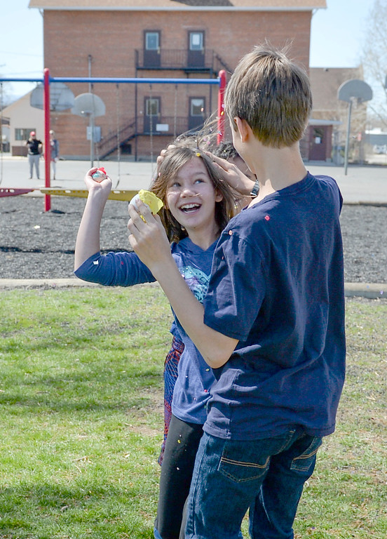 Justin Sheely   The Sheridan Press<br /> Junior high students Zia Brown and Nathan Ulery dispense shell hits during a hunt for Mexican Cascarones Easter Eggs Thursday at Holy Name Catholic School. Students from spanish language studies made the cascarones by emptying eggs then filling them with confetti. The confetti-filled eggs are part of hispanic tradition that involves cracking the eggs over a person's head. The showering of the confetti is said to bring good luck and good fortune to the recipient. In a religious context, the eggs represent the empty tomb and the resurrection of Jesus.