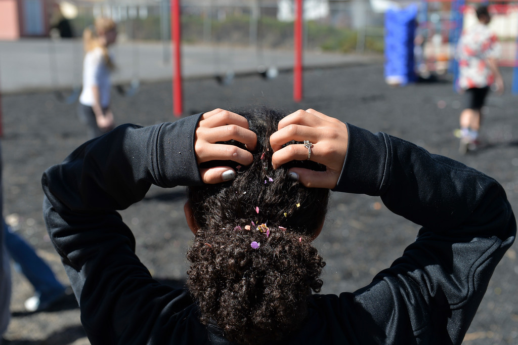 Justin Sheely   The Sheridan Press<br /> Layne Sweeney brushes confetti out of her hair during a hunt for Mexican Cascarones Easter Eggs Thursday at Holy Name Catholic School. Students from spanish language studies made the cascarones by emptying eggs then filling them with confetti. The confetti-filled eggs are part of hispanic tradition that involves cracking the eggs over a person's head. The showering of the confetti is said to bring good luck and good fortune to the recipient. In a religious context, the eggs represent the empty tomb and the resurrection of Jesus.