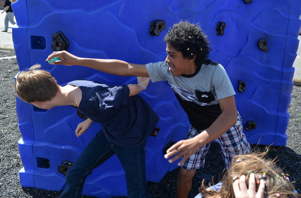 Justin Sheely   The Sheridan Press<br /> Junior high students Nathan Ulery runs away as Zach Luedtke attempts a shell hit during a hunt for Mexican Cascarones Easter Eggs Thursday at Holy Name Catholic School. Students from spanish language studies made the cascarones by emptying eggs then filling them with confetti. The confetti-filled eggs are part of hispanic tradition that involves cracking the eggs over a person's head. The showering of the confetti is said to bring good luck and good fortune to the recipient. In a religious context, the eggs represent the empty tomb and the resurrection of Jesus.