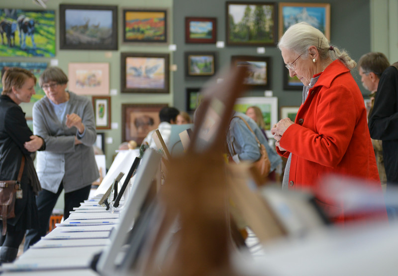 Justin Sheely | The Sheridan Press<br /> Lola Pheasant bids on art during the Gala for the Miniature Art Auction Friday at Expression Art Gallery on Broadway. The fundraiser supports the Wyoming Wilderness Association, a nonprofit conservation organization.