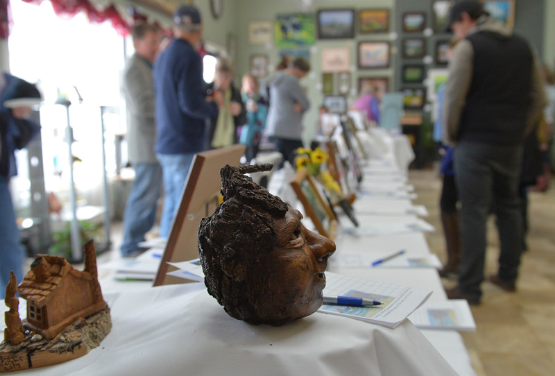 Justin Sheely | The Sheridan Press<br /> Visitor bid on art during the Gala for the Miniature Art Auction Friday at Expression Art Gallery on Broadway. The fundraiser supports the Wyoming Wilderness Association, a nonprofit conservation organization.