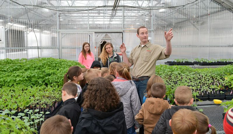 Justin Sheely | The Sheridan Press<br /> Holly Seed employee Derek Schreinhert explains the function of the greenhouse to a group of Coffeen Elementary first-graders during a field trip at Holly Seed Friday morning. Students toured the greenhouse and planted cucumber seeds into pots to bring back to their classrooms.