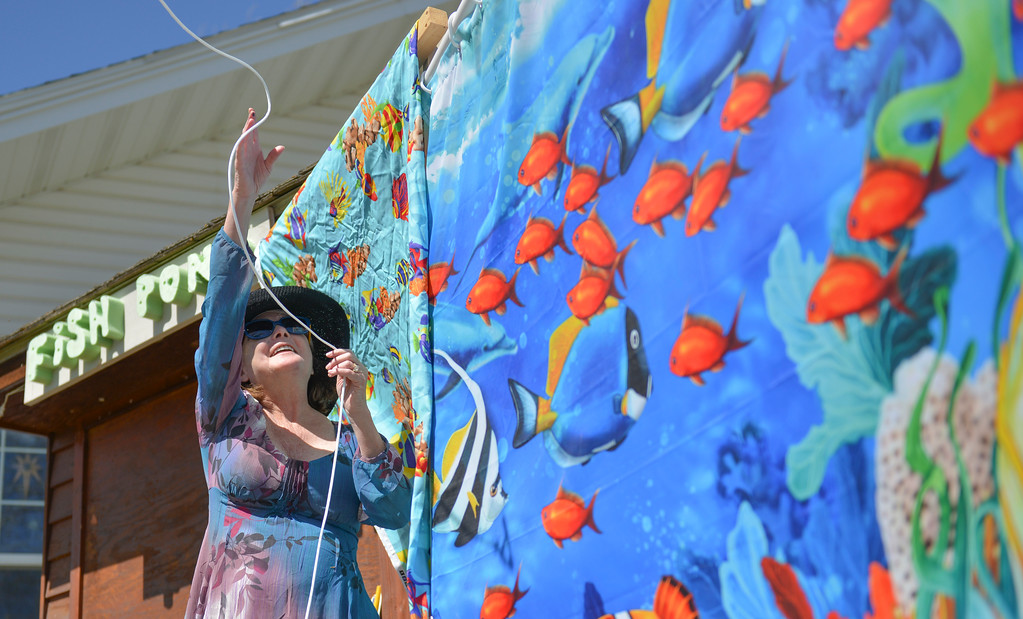 Justin Sheely | The Sheridan Press<br /> Volunteer Carol Doughty casts a line over the fish pond curtain for a child during the Easter event Saturday at Grace Anglican Church.