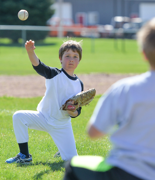 Justin Sheely | The Sheridan Press<br /> Dominic Destefano practices throwing from a kneeling position during Sheridan Recreation District's Spring Baseball Clinic Saturday at Oatts Field in Sheridan.