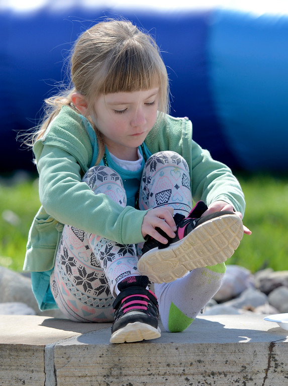 Justin Sheely | The Sheridan Press<br /> Five-year-old Aspen Booth puts her shoes back on after an inflatable ride during the Easter event Saturday at Grace Anglican Church.