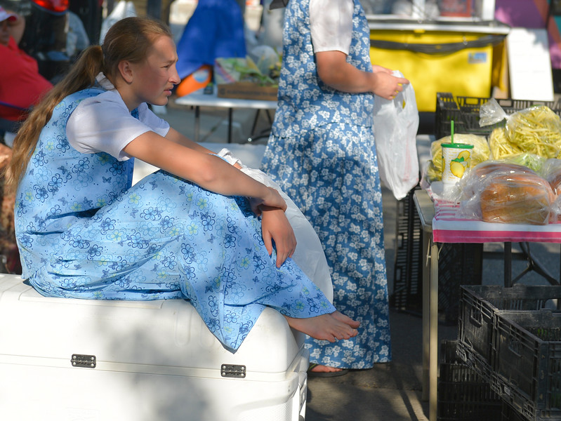 Justin Sheely | The Sheridan Press<br /> Fourteen-year-old Monique Walter of Lodge Grass, Montana, sits on a cooler during the weekly Farmers Market Thursday on Grinnell Plaza. The Farmers Market is every Thursday from 5 – 7 p.m.