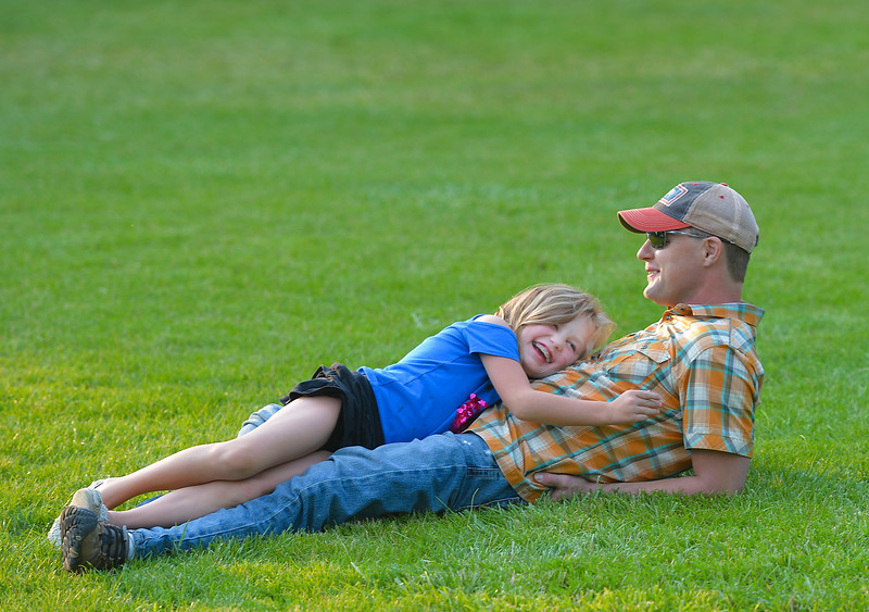Justin Sheely | The Sheridan Press<br /> Seven-year-old Avann Johnson and Mark Johnson lay on the grass during the Concert in the Park Tuesday at Kendrick Park. This was the last night the community band met for Concerts in the Park this summer. The Crossroad Station of Ohio will perform Aug. 15, and Orchard Fire of Nashville, Tennessee, will play on the final night on Aug. 22.
