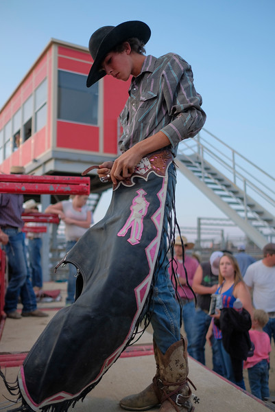 Justin Sheely | The Sheridan Press<br /> Brian Harrison pulls on his chaps before bull riding during the Sheridan County Rodeo Saturday at the Sheridan County Fairgrounds.