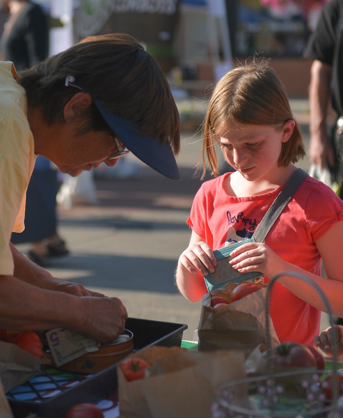 Justin Sheely | The Sheridan Press<br /> Eight-year-old Maddie Thompson buys some tomatoes during the weekly Farmers Market Thursday on Grinnell Plaza. The Farmers Market is every Thursday from 5 – 7 p.m.