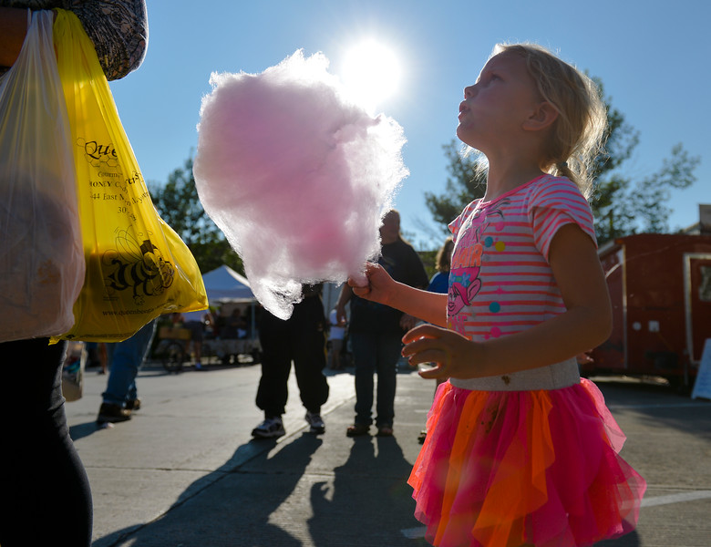 Justin Sheely | The Sheridan Press<br /> Four-year-old Libby Kennedy gets a stick of cotton candy during the weekly Farmers Market Thursday on Grinnell Plaza. The Farmers Market is every Thursday from 5 – 7 p.m.