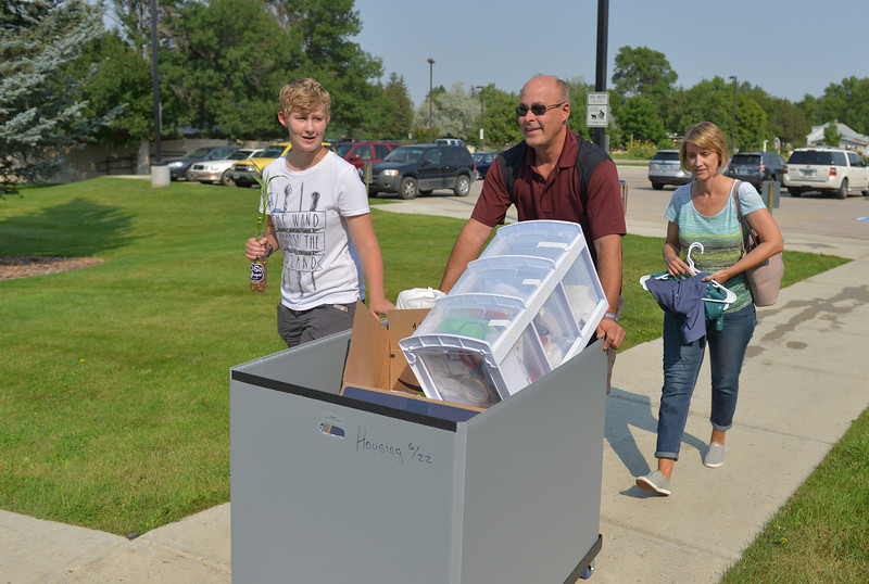 Justin Sheely | The Sheridan Press<br /> Incoming freshman student Sara Heili, left, and parents Wayne Heili and Stacie Heili push a cart to student housing during student move-in day Friday morning at Sheridan College. Classes begin Aug. 28.