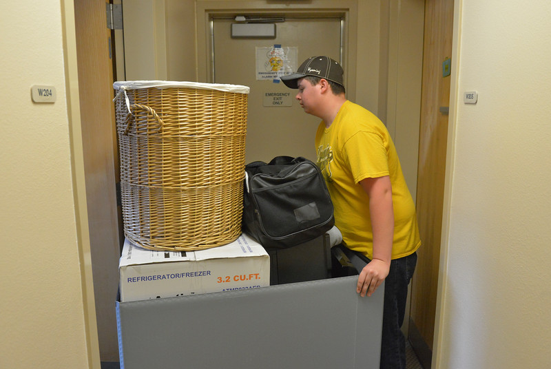 Justin Sheely | The Sheridan Press<br /> Incoming freshman student Jordan Hartman pushes a cart of his things into his room during student move-in day Friday morning at Sheridan College. Classes begin Aug. 28.