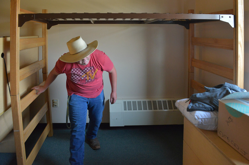 Justin Sheely | The Sheridan Press<br /> Dillon Riley of Burlington, Wyoming, ducks as he sets up his bunk bed during student move-in day Friday morning at Sheridan College. Classes begin Aug. 28.