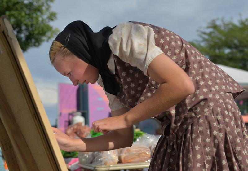 Justin Sheely | The Sheridan Press<br /> Young Hutterite Joyce Walter of the 40 Mile Colony Ranch near Lodge Grass, Montana, writes prices during the weekly farmers market Thursday afternoon on Grinnell Plaza.